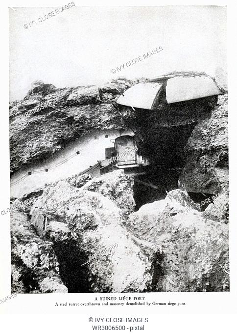 This photo from soon after August 5, 1914, shows a ruined liege fort during World War I. Here a steel turret is shown overthrown and the masonry dmonlished by...