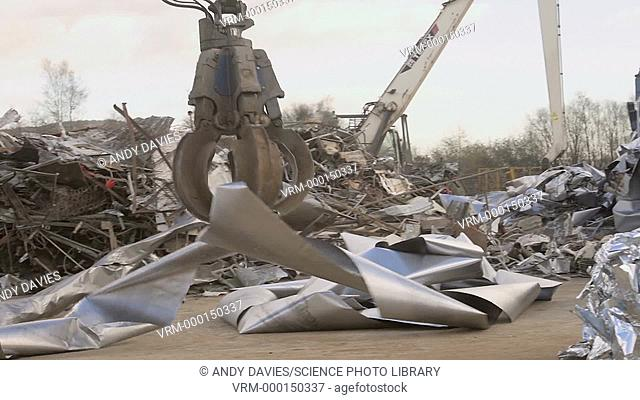 A machine lifting and moving pieces of scrap metal in a scrap yard