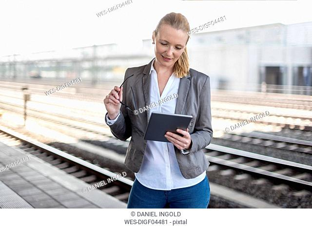 Mature businesswoman waiting at platform using tablet