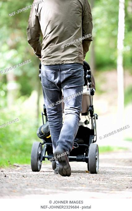 Man walking with pram, low section