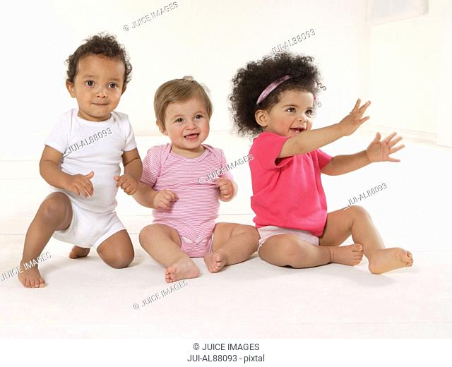 Three babies sitting on floor
