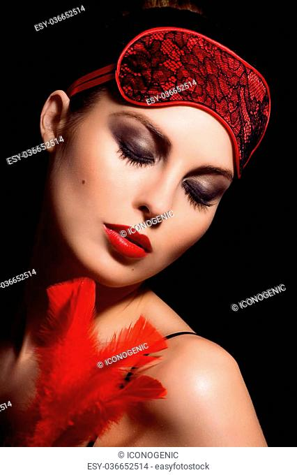 Beautiful woman with ref feather, red lipstick and red blindfold