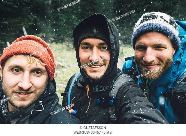 Canada, British Columbia, Yoho National Park, selfie of three smiling hikers in snowfall
