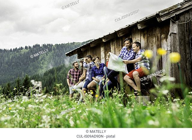 Group of friends chatting and reading map, Tirol, Austria