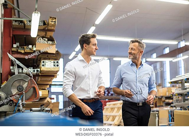 Two businessmen walking and talking in factory storeroom