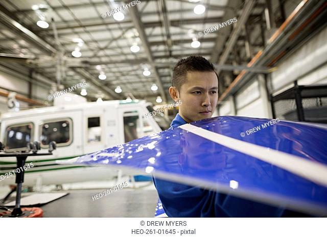Mechanic examining helicopter panel in airplane hangar