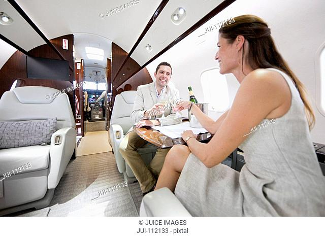 Smiling couple drinking champagne in private jet