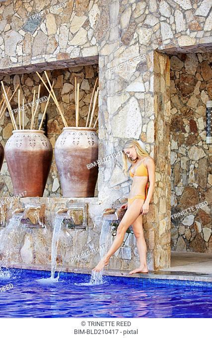Caucasian woman dipping foot in swimming pool