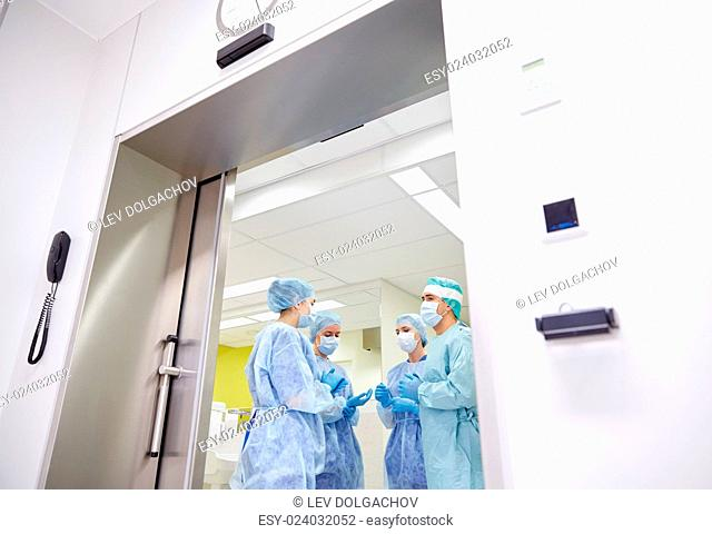 surgery, medicine and people concept - group of surgeons in operating room at hospital talking and preparing to operation