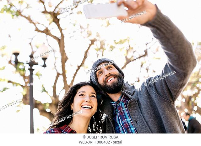 Young happy couple taking a selfie outdoors