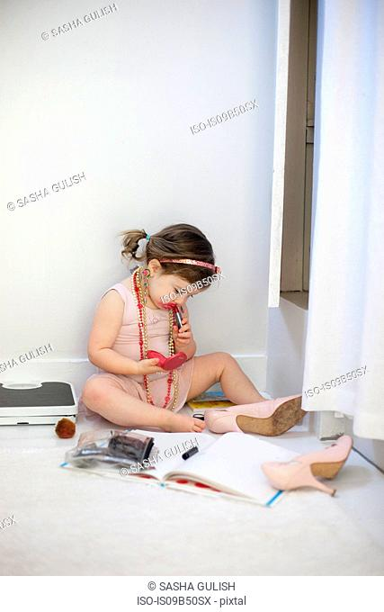 Girl dressing up, playing with lipstick