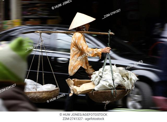 Woman on a busy street carrying baskets, Hanoi, North Vietnam