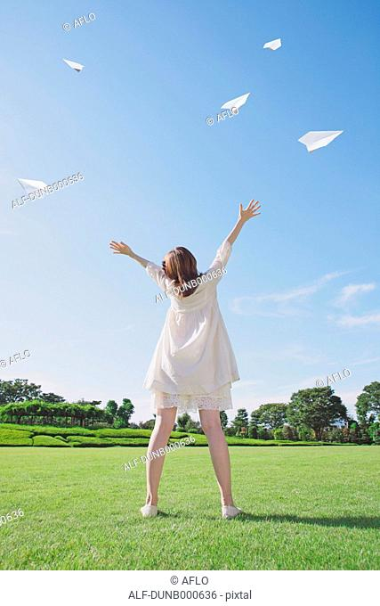 Japanese woman flying paper planes in a city park