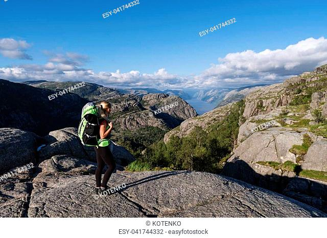 Tourist with a backpack on pathway Pulpit Rock. Blond girl in a mountain trek. View of Lysefjord, Norway