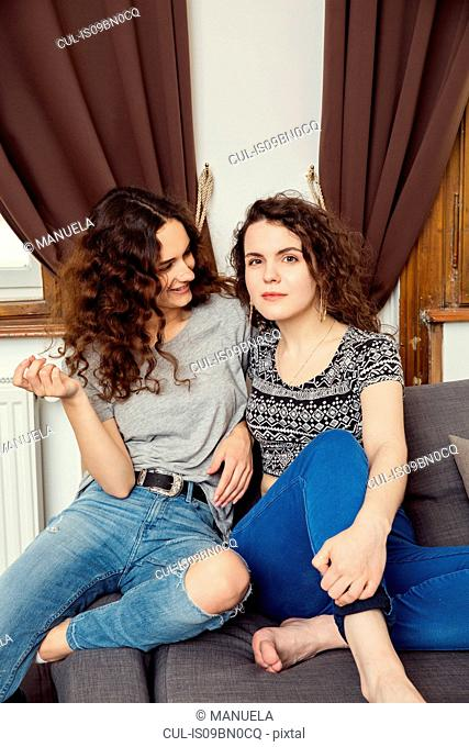 Two young female friends sitting on sofa portrait