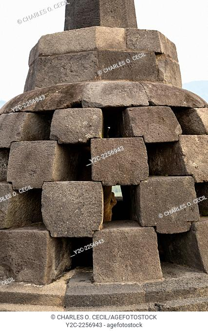 Borobudur, Java, Indonesia. Close-up of a stupa on the upper level of the temple. The square-shaped holes symbolize the overcoming of passions as one approaches...
