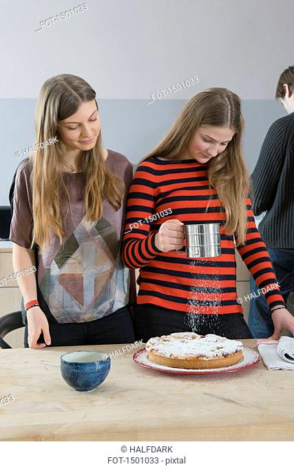 Young woman watching sister sprinkling tart with icing sugar at home