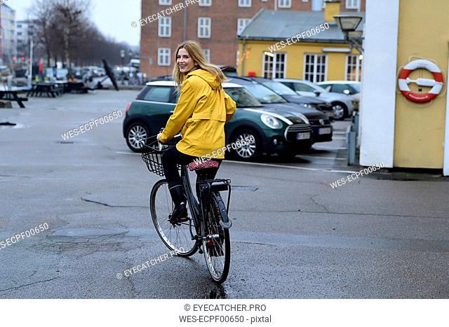 Denmark, Copenhagen, happy woman riding bicycle on waterfront promenade in rainy weather