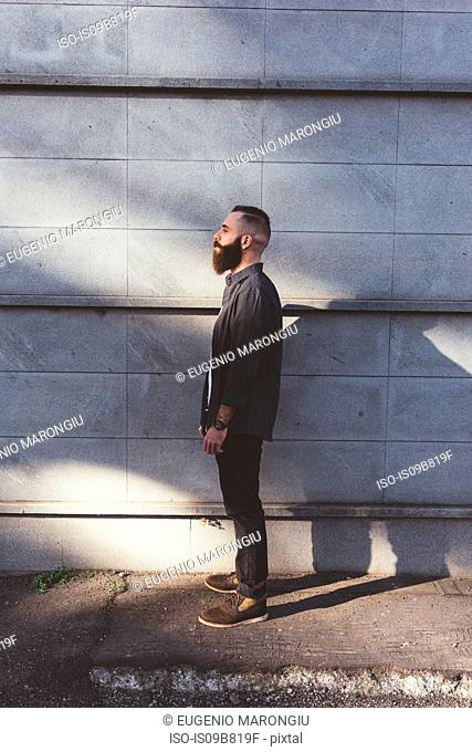 Full length side view portrait of bearded man