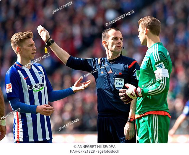 Hertha's Mitchell Weiser (L)gestures as referee MarcoFritz (C)looks to Munich's goalkeeper Manuel Neuer (R) during the German Bundesliga soccer match between...