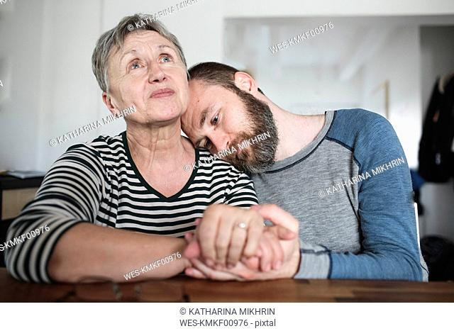 Affectionate adult son with senior mother at home