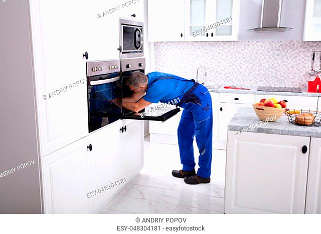 Mature Technician In Overall Repairing Oven In Kitchen