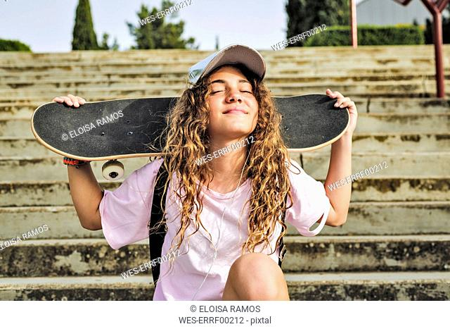 Girl with skateboard sitting on steps