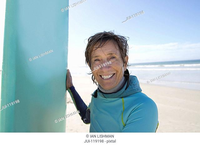 Senior surfer with board on sandy beach