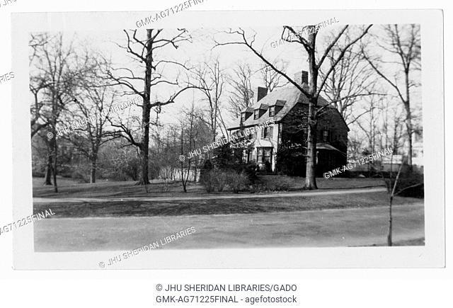 Landscape shot of a house from a distance with multiple stories, two chimneys, large front and back yards, surrounded by trees without leaves