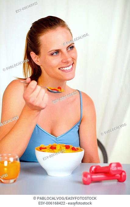 Portrait of a lovely pretty girl smiling and eating healthy breakfast at home indoor