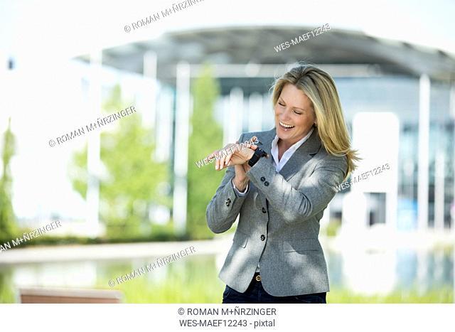 Happy businesswoman using smartwatch outdoors
