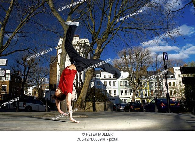 man doing back flip on street