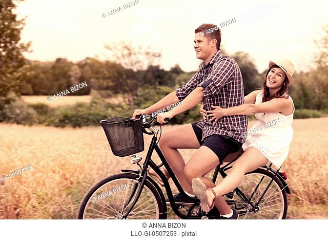 Couple have fun riding on bike, Debica, Poland
