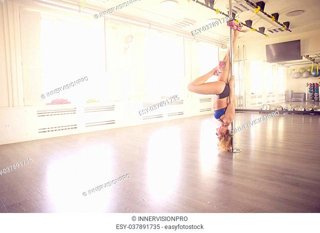 A photo of young woman training on dance pole. She's hanging upside down, doing acrobatics