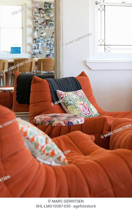 Throw pillows on modern orange lounge chairs