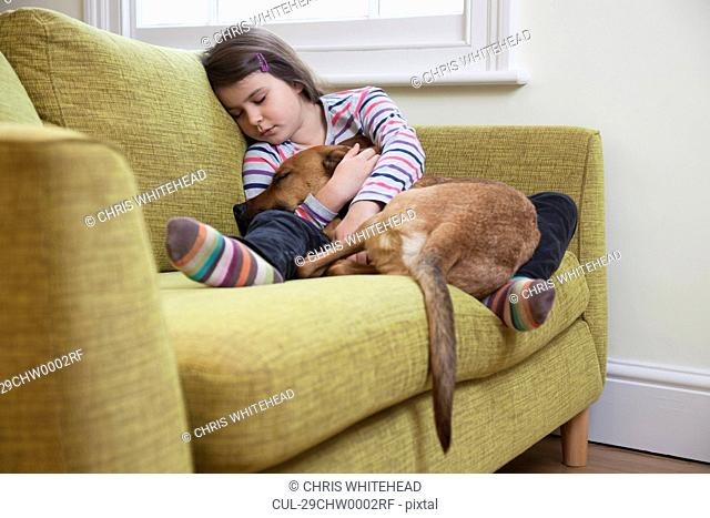 Young girl sleeping with her dog