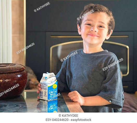 smiling happy hispanic boy sitting in living room next to table with a milk carton