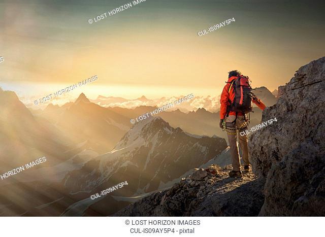 Climber watching a mountain range at sunset, Alps, Canton Wallis, Switzerland