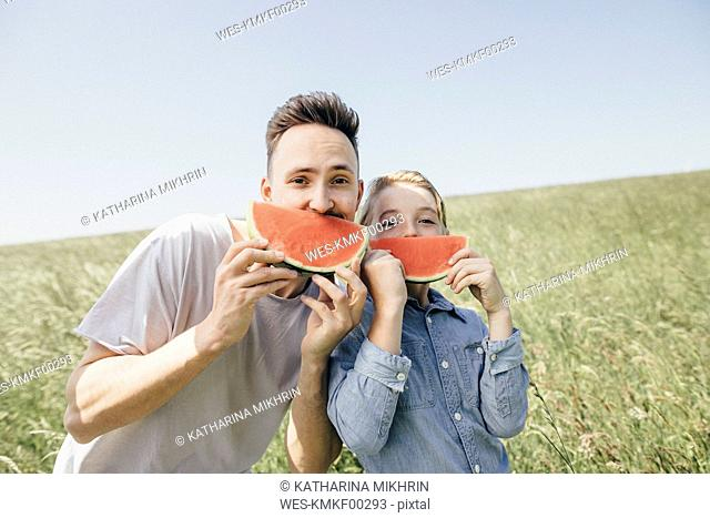 Portrait of young man and boy on a field holding watermelons