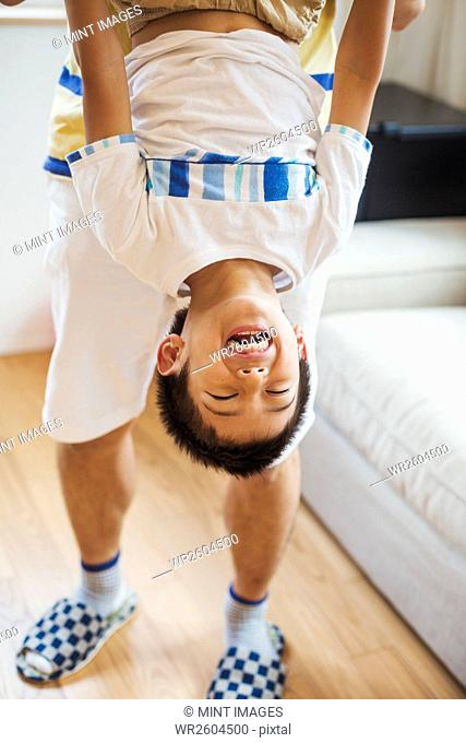 Family home. A man holding his son upside down playing