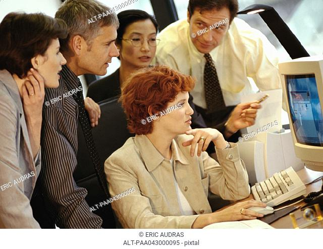 Five business people grouped around computer screen