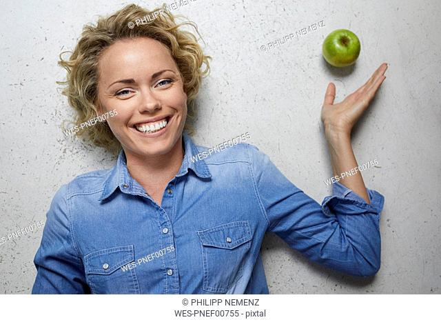 Portrait of happy blond woman with green apple