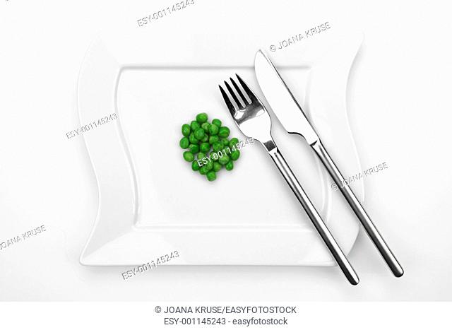 a bunch of peas on a white plate with fork and knife