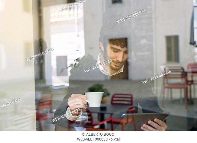 Young man in a cafe looking at digital tablet