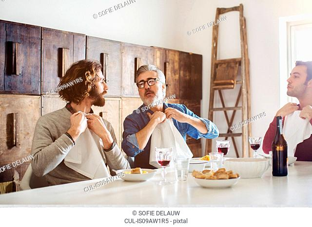 Mature man and adult sons tucking in napkins for lunch at dining table