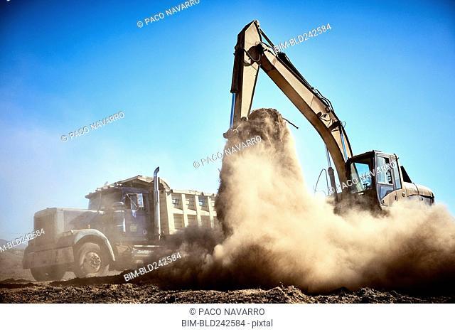 Truck near digger in dirt field