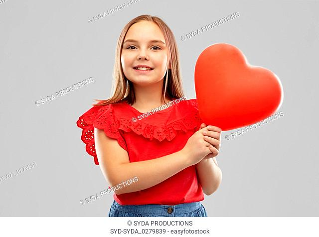 smiling girl with red heart shaped balloon
