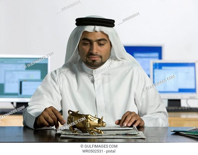 Arab man looking at the bull figurine on top of the table