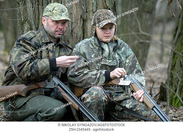 Young girl on the hunt with an experienced instructor in the forest