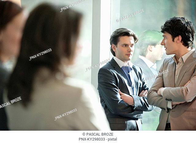 Two businessmen discussing each other